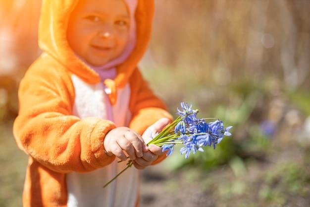 日光の下で屋外の春の花を持つ魅力的な幼児