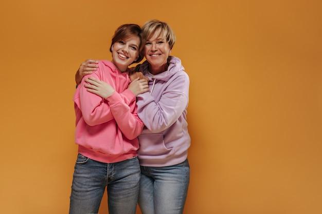 Affascinanti due donne con sorrisi adorabili e acconciatura corta e fresca in moderne felpe rosa e jeans alla moda che abbracciano su uno sfondo isolato.
