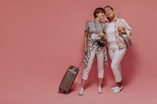 Affascinanti due donne con acconciatura corta e fresca in abiti moderni leggeri in posa con biglietti, macchina fotografica e valigia e sorridenti su sfondo rosa.