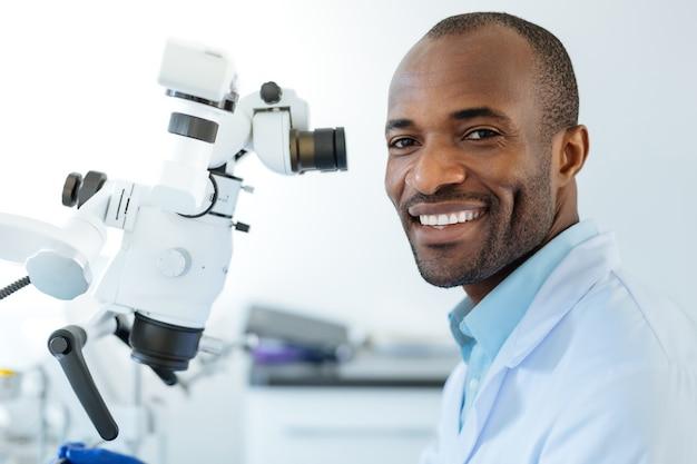 Очаровательный оптимистичный стоматолог позирует и ярко улыбается, используя микроскоп на работе и проводя обследование