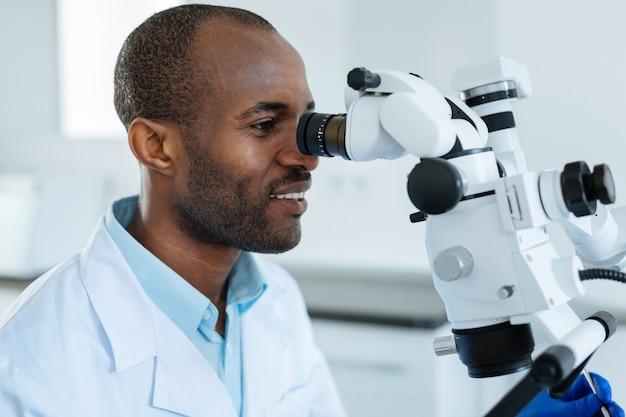 Очаровательный жизнерадостный стоматолог изучает ротовую полость своего пациента с помощью микроскопа, обнаруживая микротрещины в зубах.