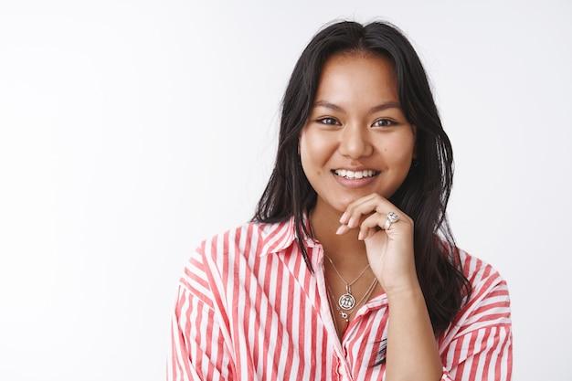 Affascinante donna vietnamita con tatuaggio che ascolta con entusiasmo e gioia avendo una conversazione interessante toccando il labbro dalla curiosità sorridendo ampiamente in posa incuriosito su sfondo bianco