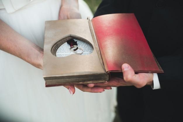 반지가 놓여있는 수제 하트가있는 매력적인 빈티지 책. 세련된 디자인.