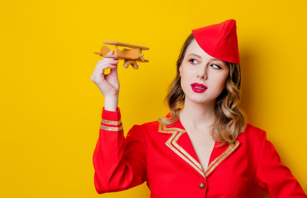 Charming vintage stewardess wearing in red uniform with airplane