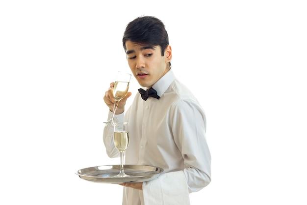 와인과 불가사의 한 잔을 들고 흰 셔츠에 매력적인 웨이터는 흰 벽에 격리됩니다