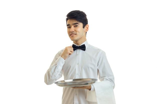 트레이를 들고 흰 셔츠에 매력적인 웨이터와 흰 벽에 고립 된 그의 활을 조정