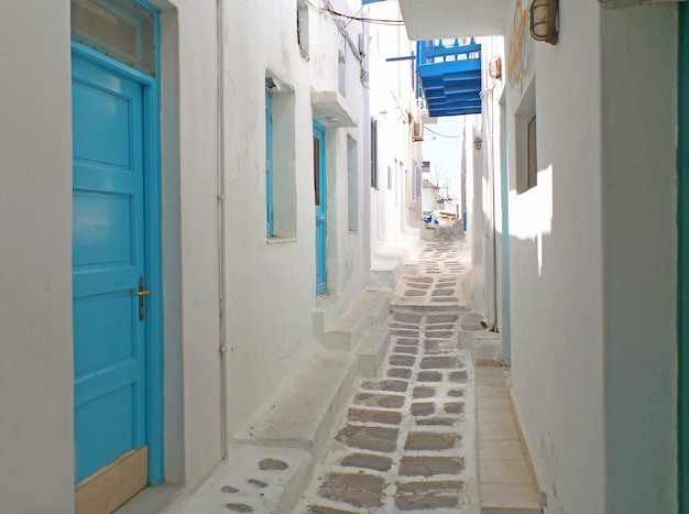 Charming white and blue buildings with small alley leading to chora windmills, mykonos, greece