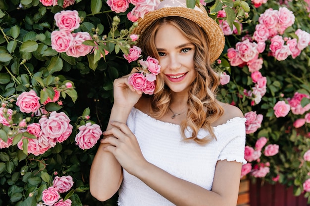 Charming white female model standing in front of pink flowers. outdoor portrait of joyful girl in trendy hat spending time in garden.