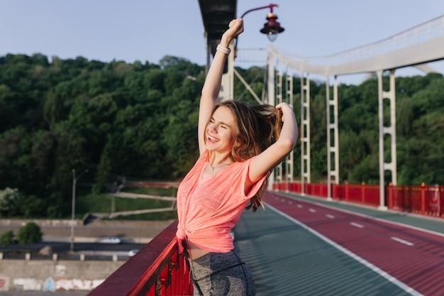 Очаровательная белая девушка растягивается и смеется. портрет веселой женщины, танцующей на стадионе.