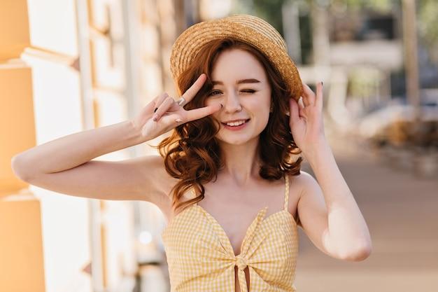 Очаровательная белая женщина в винтажном платье, выражающем счастье в летний день. наружное фото модной дамы имбиря в шляпе, смеющейся над городом.