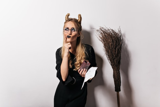 Charming witch in glasses posing on white wall. indoor photo of pensive vampire girl enjoying halloween party.
