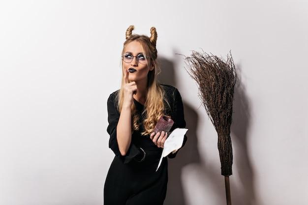 흰 벽에 포즈 안경에 매력적인 마녀. 할로윈 파티를 즐기는 잠겨있는 뱀파이어 소녀의 실내 사진.