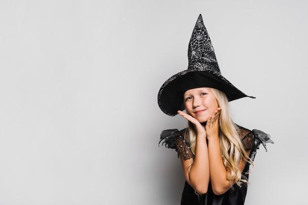 Очаровательная ведьма смотрит на камеру