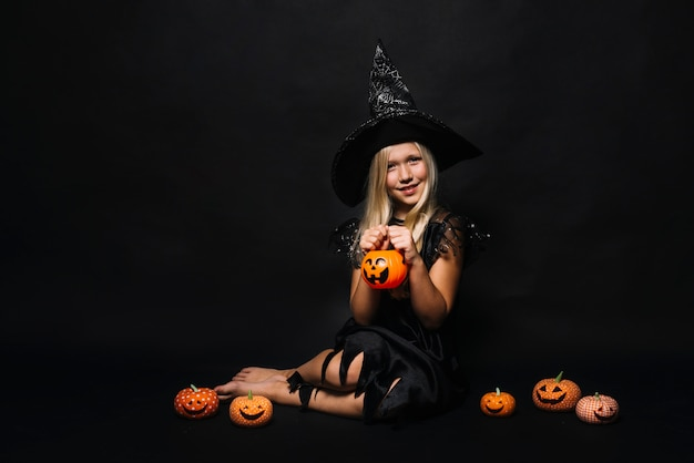 Charming witch with small jack-o-lanterns
