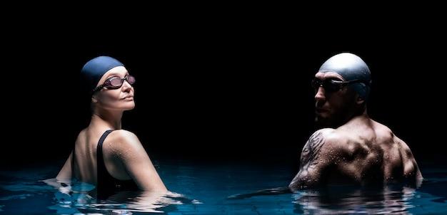 Очаровательная женщина и сильный мужчина позируют в бассейне. вид сзади.