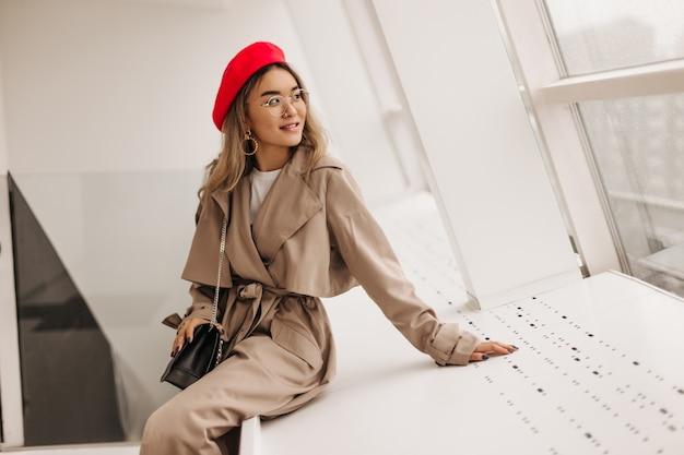 Affascinante donna in cappotto beige si siede sul davanzale bianco e guarda fuori dalla finestra
