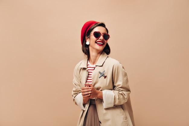 Affascinante donna in abito beige e berretto rosso ride su sfondo isolato. carina giovane signora in occhiali da sole e con labbra luminose in posa sulla macchina fotografica.