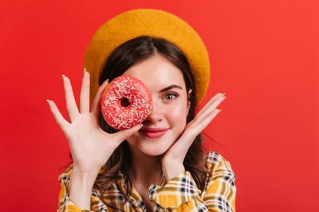 Affascinante donna in berretto in posa con ciambella sulla parete rossa. la ragazza in camicia gialla è sorridente carina.