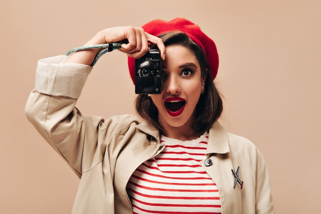 Charming woman in beret and trench takes photo on isolated background. wonderful young lady with red lips and in striped sweater is holding camera.