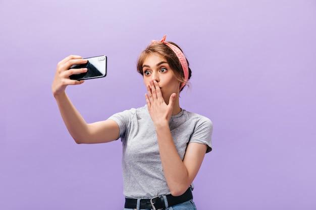Affascinante donna soffia bacio e prende selfie. divertente bella ragazza in bandana rosa e t-shirt fa foto su sfondo isolato.
