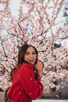Charming woman in bright sweater laughs against blossoming sakura. cool brunette woman in red outfit smiling and enjoying spring