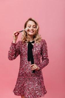 Affascinante donna in abito brillante mette arrossire utilizzando soffice pennello