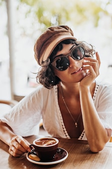 Charming woman in brown cap and sunglasses smiles in street cafe