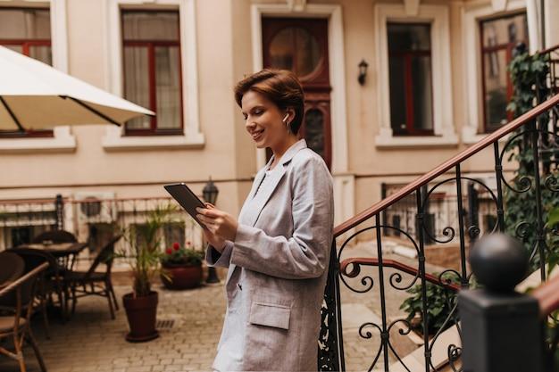 Affascinante donna in chat in tablet e in posa all'esterno. felice signora dai capelli corti in abito grigio oversize sorridente e tenendo il dispositivo