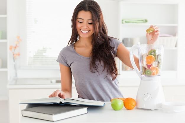 Очаровательная женщина, консалтинг ноутбук, заполняя блендер с фруктами