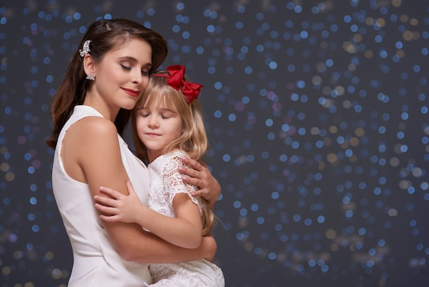Charming woman and daughter in love embrace