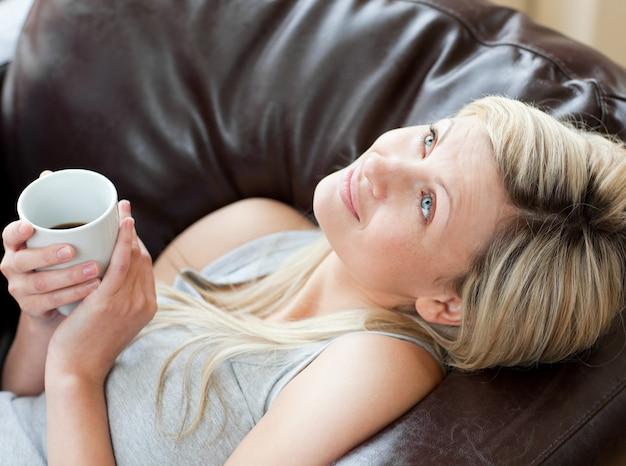 ソファーに座っているコーヒーを飲む魅力的な女性