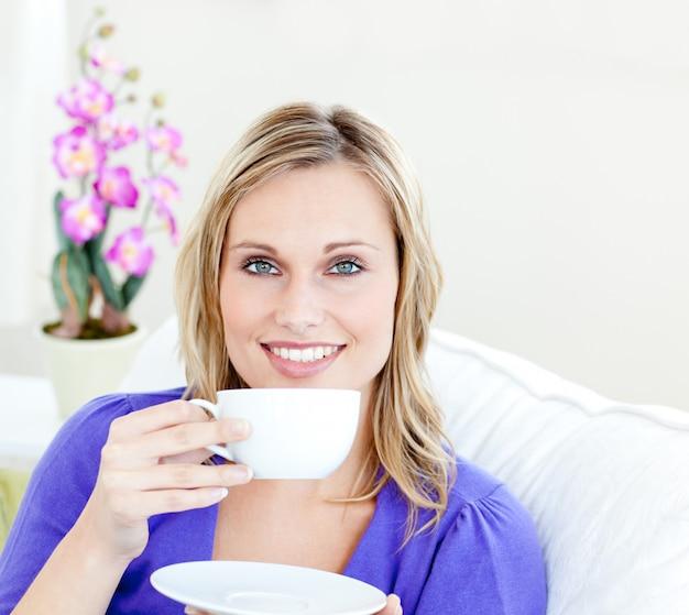 Charming woman enjoying her coffee sitting on a sofa in the livingroom