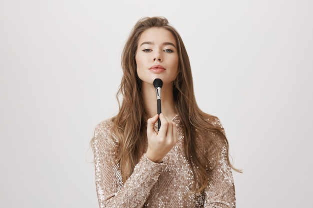 Charming woman in evening dress holding makeup brush
