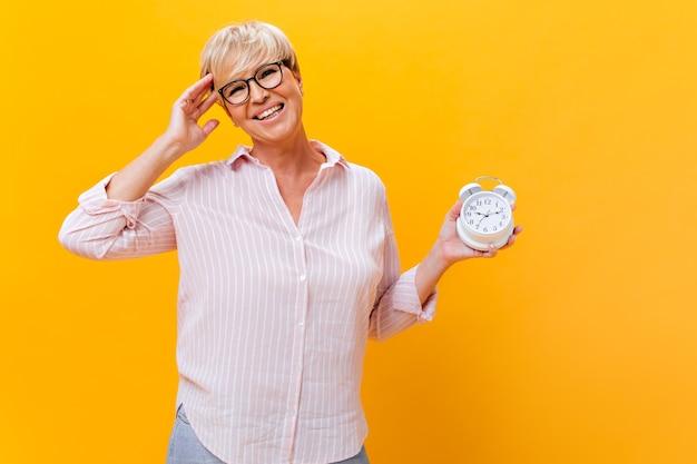 Affascinante donna in occhiali da vista e camicia rosa pone con la sveglia