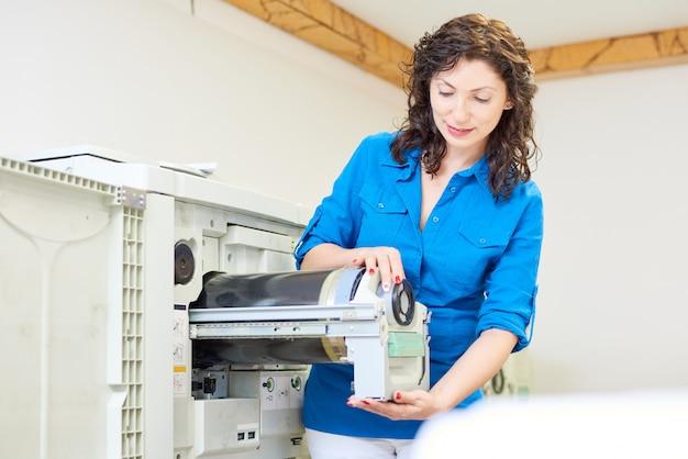 Charming woman fixing printer
