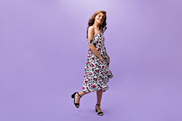 Charming woman in floral outfit dancing on purple background. cute curly girl with long hair posing into camera on isolated backdrop.