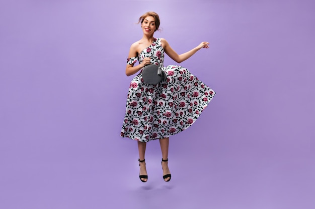 Charming woman in floral outfit jumping on purple background. attractive stylish girl in colorful trendy dress smiling with handbag.