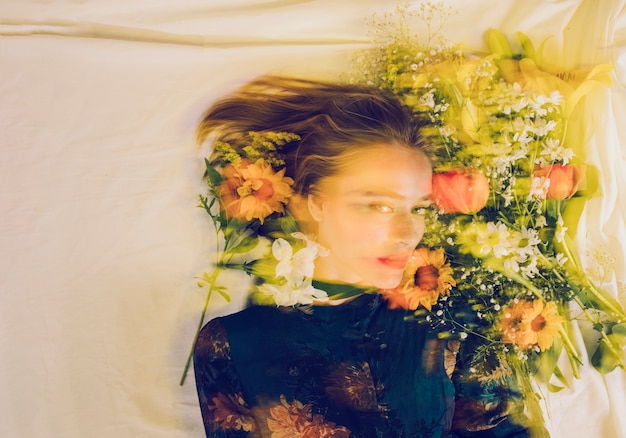 Charming woman between fresh flowers on bed