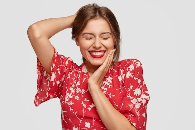 La donna affascinante ha una splendida giornata, sorride positivamente, tiene gli occhi chiusi, sorride dalla gioia, tiene la mano sulla guancia