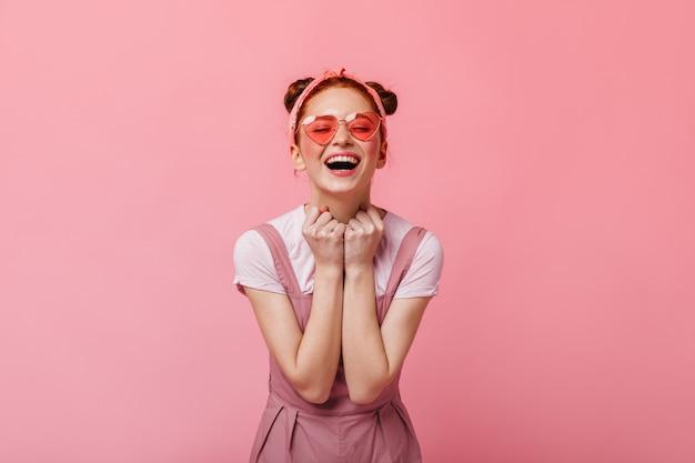 놀랍게도 매력적인 여자는 분홍색 배경에 카메라를 살펴 봅니다. 분홍색 상단과 흰색 티셔츠에 여자의 초상화.