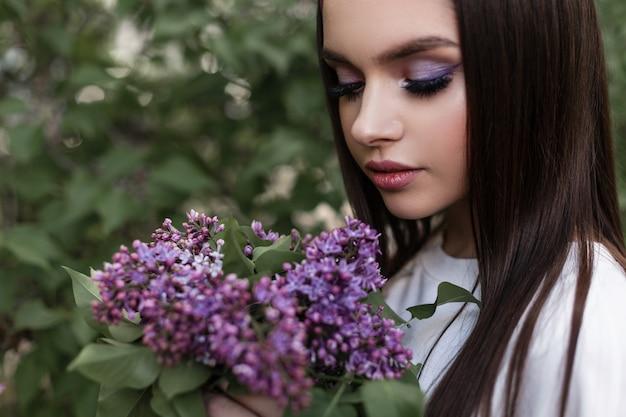 公園の緑の葉の近くに立っている驚くべき新鮮な紫色の花の花束で化粧をした白い服を着たバンダナの魅力的な女性。かわいい女の子は花束を見て、美しさとライラックの香りを楽しんでいます。