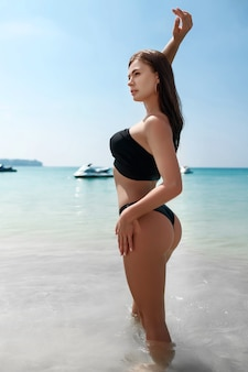 手を上げて海岸でポーズをとるビキニの魅力的な女性