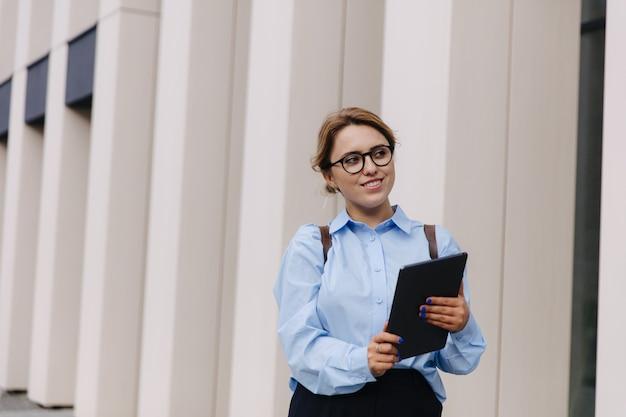 파란색 셔츠, 검은 바지, 안경 손에 디지털 태블릿 거리에 서있는 매력적인 여자. 도시 생활과 현대적인 가제트.