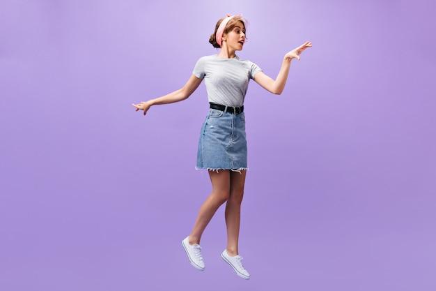 デニムスカートの魅力的な女性が紫色の背景にジャンプします。ピンクのヘッドバンドと灰色のシャツのポーズでファッショナブルなかわいい女の子。