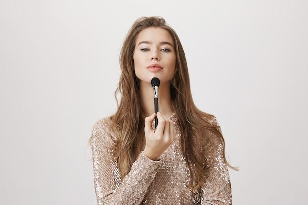 化粧ブラシを保持しているイブニングドレスの魅力的な女性