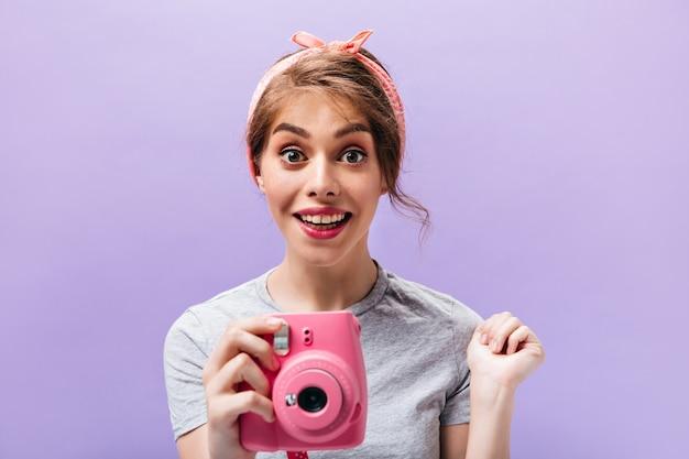 Очаровательная женщина в серой рубашке держит розовую камеру. счастливая красивая девушка с летней повязкой на голову в стильной одежде позирует на изолированном фоне.