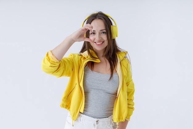 ハーフハートのシンボルをやっているヘッドフォンの魅力的な女性