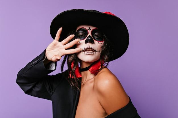 頭蓋骨の形をしたマスクの魅力的な女性が不思議なポーズをとり、手で顔を覆っています。帽子をかぶった女性の肖像画。