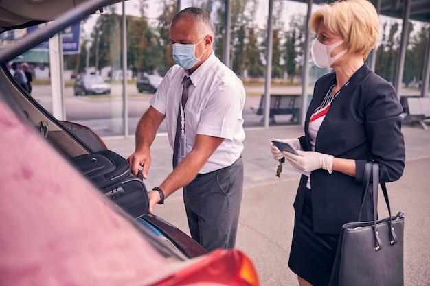 남자가 자동차 트렁크에 여행 가방을 배치하는 동안 티켓과 여권을 들고 의료 마스크에 매력적인 여자