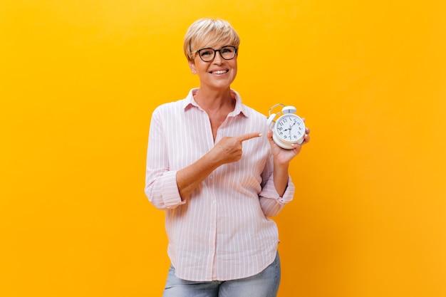 Очаровательная женщина в розовой рубашке, указывая на будильник на оранжевом фоне